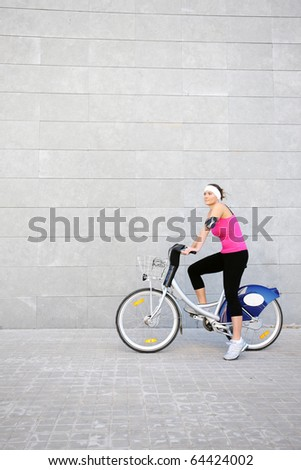 A picture of a young girl on a bike over grey urban background