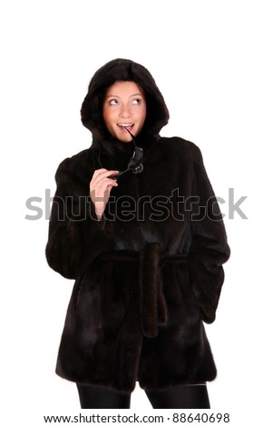 A picture of a young glamour woman standing in a mink coat over white background