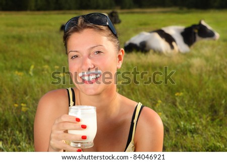 A picture of a young happy woman drinking fresh milk on the meadow cow in the background