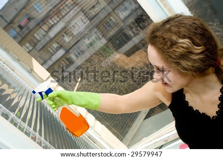 A picture  of a  young  pretty  woman in  green gloves doing her housework - cleaning a window with a spray