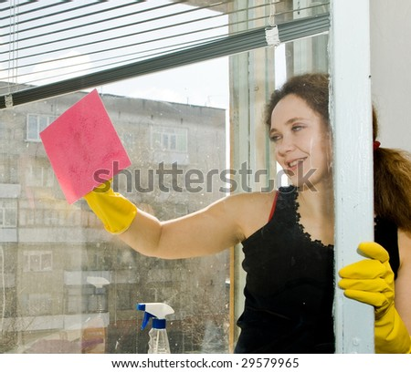 A picture  of a  young  pretty  woman in  yellow gloves doing her housework - cleaning a window with a red  rag