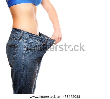A picture of a young slim woman in oversized pair of blue jeans over white background