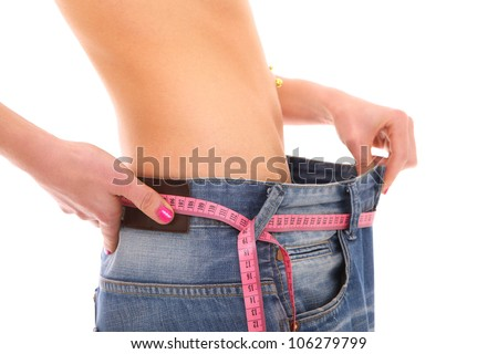 A picture of a young woman in loose jeans showing effects of diet over white background