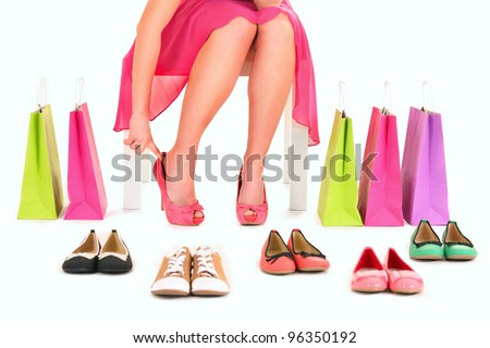 A picture of a young woman trying on new pair of heels over white background