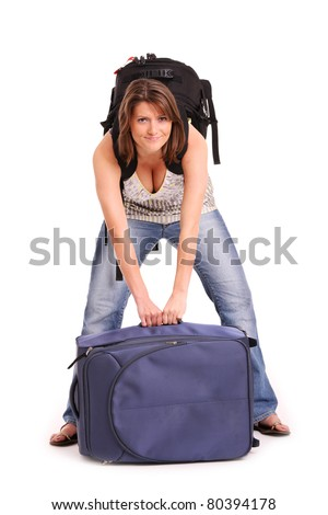 A picture of a young woman trying to lift a heavy suitcase over white background