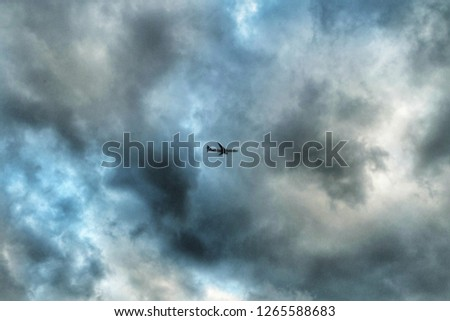 A picture of an aeroplane flying at th cloudy sky in London, United Kingdom.