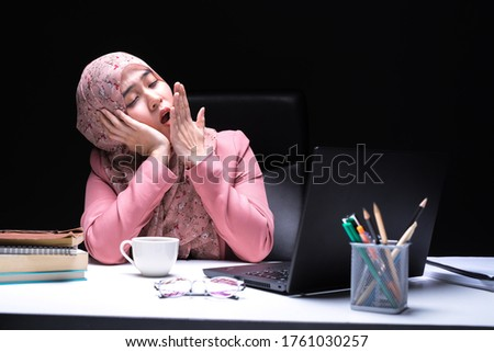 A picture of an office worker, a Muslim woman sitting overtime working at the office with a weary and sleepy face. Stock photo ©