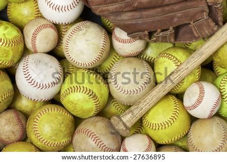 a picture of baseballs, softballs, a bat and glove