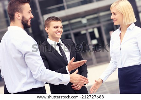 A picture of business people greeting outside modern building