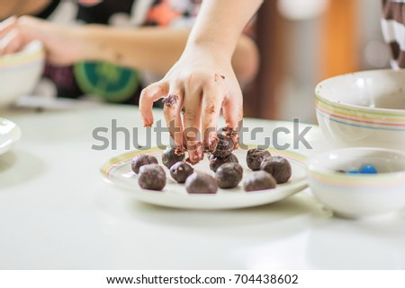 A picture of child's hand try to making chocolate cake pops recipe.