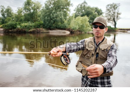 A picture of cool guy stands in water and fishing. He holds fly-fishing with reel under it in one hand and spoon from it in the other one. Guy looks straight. He wears sunglasses.