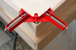A picture of corner clamp clipping a word during making furniture.