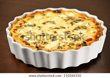 A picture of freshly baked vegetable quiche in a white tin over wooden surface