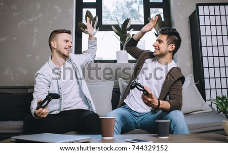 A picture of good teamwork during the game. Two friends are sitting on the sofa and clapping each other hands. They have played the best game ever and they really happy about that.