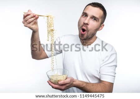 A picture of guy that likes to eat oriental cuisine. He has a plate of thai spaghetti and keep it with special sticks for food. Also this weird guy likes to eat junk food. Isolated on white background