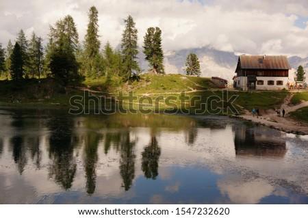 A picture of mountain cottage rifugio Croda da Lago and line of trees reflected in the water of the lake Lago di Federa near Cortina d'Ampezzo, Dolomites, Italy Foto d'archivio ©