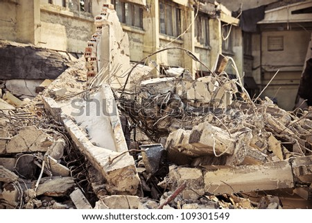 A picture of o heap of rubble and a demolished building in the background