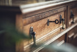 A picture of old oak wood chest of drawers with a key in the keyhole. Shallow DOF