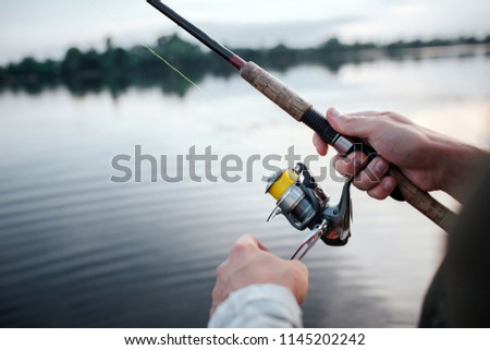 A picture of rotative spinner that guy holds in hands. He rotates reel with left hand. He is at lake. It is evening outside.