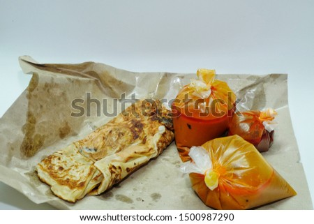 "A picture of ""roti sardin"" or sardine prata famous in Malaysian restaurant with curry, spicy sauce and dal."