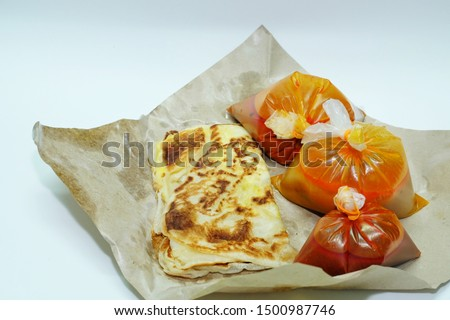 "A picture of ""roti telur"" or egg prata famous in Malaysian restaurant with curry, spicy sauce and dal."