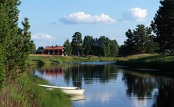 A picture of rural Swedish countryside. A traditional red house (stuga) in the background, and a boat on a lake. An idyllic landscape of Dalarna, Sweden. A summer view of Malung.
