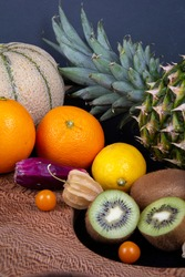 A picture of some delicious fruits in a frame. Honeydew melon, pineapple, some kiwifruits, oranges, lemons and some Chinese lantern fruits.