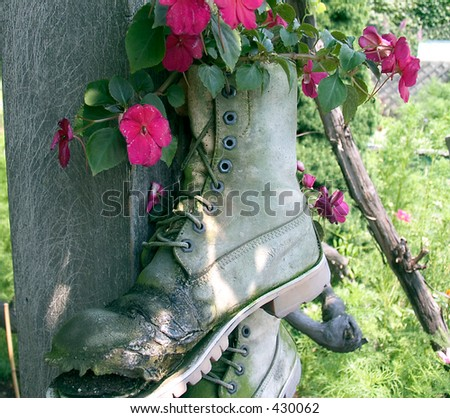 A picture of the old boot used as a hanging flower pot.