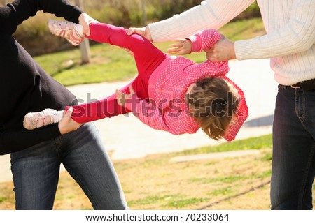 A picture of two adults fighting for an innocent child in the park