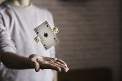 A picture of two dice and an Ace of Spades card levitating in a person's palm