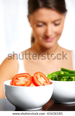 A picture of two white bowls of vegetables with a young wife in the background