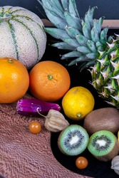 A picture of various fruits. Honeydew melon, pineapple, some kiwifruits, oranges, lemons, Barbary fig and some Chinese lantern fruits.