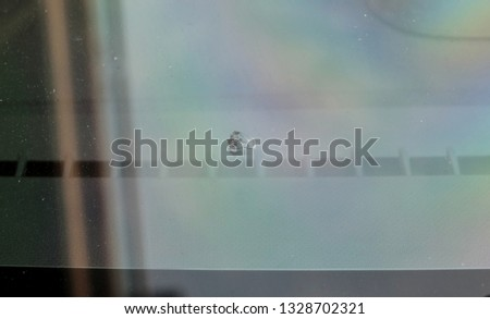A picture of windshield chip that been hit by a stone.