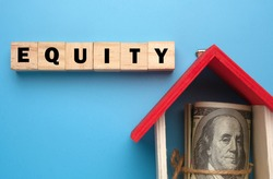 A picture of wooden block with Equity word, house miniature and fake money insight. Equity is the difference between the market value of your home and the mortgage amount.