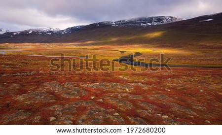 A picture taken with a drone of Kungsleden trail between Abiskojaure and Tjaktja, stupendous autumn colors, September 2020. Stock photo ©