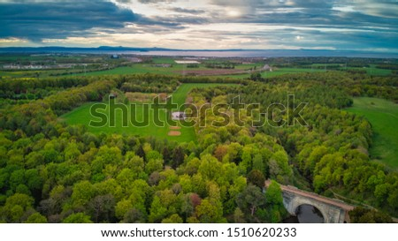 A picturesque aerial view of a green park with old arch bridge under a blue cloudy sky - Dalkeith country park #1510620233