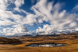A picturesque bright autumn landscape with a beautiful lake, mountains covered with snow, clouds and reflections on a background of blue sky in the early morning