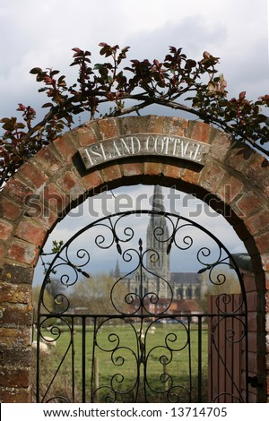 A picturesque cottage gate with arched brick work above covered with a climbing rose, with a view of Salisbury Cathedral visible through the wrought iron gate.