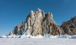 A picturesque granite rock, devoid of vegetation, rise above a frozen lake. There are cracks on the stones. There is a layer of icicles at the base. Clear blue sky. Baikal
