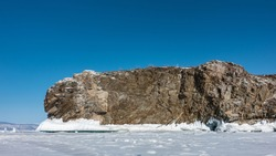 A picturesque granite rock, devoid of vegetation, rises above a frozen lake. There are cracks on the stones. The base is covered with icicles. Clear blue sky and white snow on the ice. Baikal