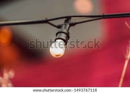 a picturesque light bulb in front of a background in which the primary color is faded.