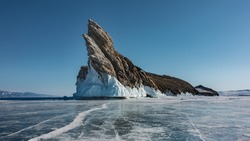 A picturesque rocky island devoid of vegetation rises in the middle of a frozen lake. Bizarre outlines, sharp tops, icicles at the base. There are cracks in the ice. Clear blue sky. Baikal