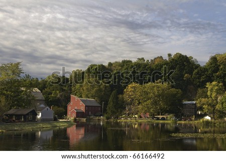 A picturesque rural view is made by historic red mill and riverside village buildings;