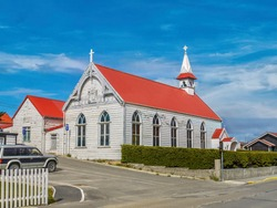 A picturesque scene in Stanley, Falkland Islands, with an exterior view of St. Mary's Church, set against a vibrant blue sky.