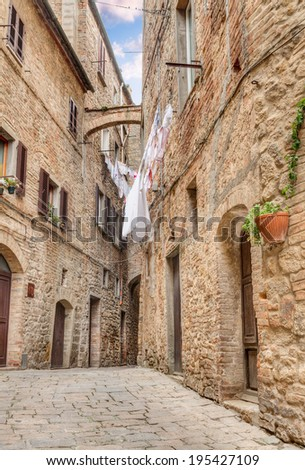 a picturesque typical corner with clothes hanging in the old town of Volterra, Tuscany, Italy