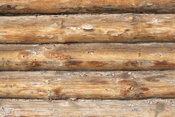 A piece of a wall in a house made of logs. Wood texture is seen distinctly