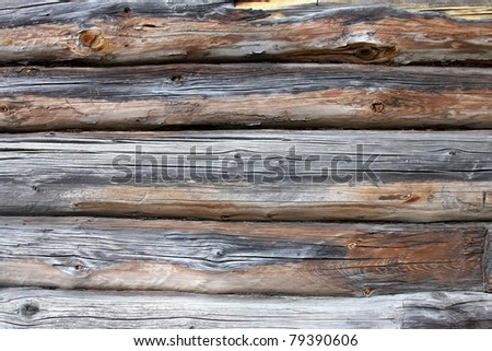 A piece of a wall in a old house made of logs. Wood texture is seen distinctly