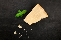 A piece of aged Parmesan cheese with crumbs, shot from the top on a black background with fresh basil leaves and a place for text