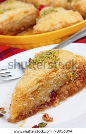A piece of baklava from Turkey or Greece with pistachio nuts, filo pastry and syrup. Close-up view. - stock photo