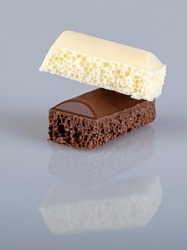 A piece of black and a piece of white porous chocolate on top of each other, isolated on a white background with reflection